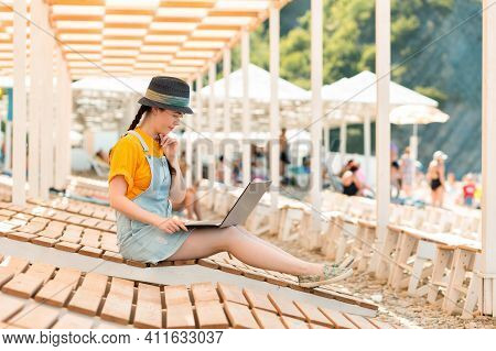 Freelance. A Young Woman Sits On A Sunbed And Thoughtfully Works At A Laptop. Sun Beds And Umbrellas