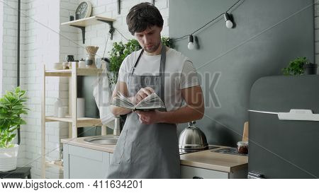 Man Cooking In Kitchen Reading Recipe From Cookery Book.