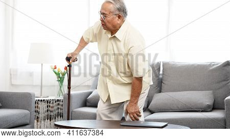 Asian Eldery Senior Man Feeling Pain In Knee And Standing Up Step Walking The Floor With A Cane At H