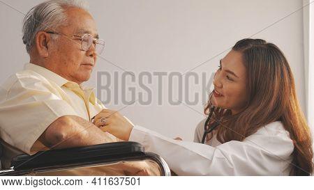 Female Nurse Doctor In Uniform Health Check Senior Grandfather Patient At Home Medical Visit, Elderl