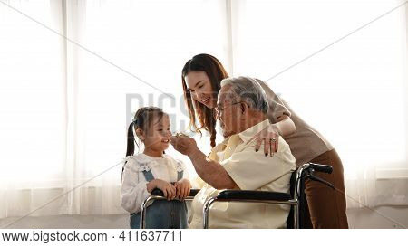 Happy Family Multi-generation Mother And Daughter Taking Care Of The Senior Grandfather In The House