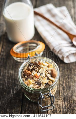 Beakfast cereals in jar. Healthy muesli with oat flakes, nuts and raisins on wooden table.
