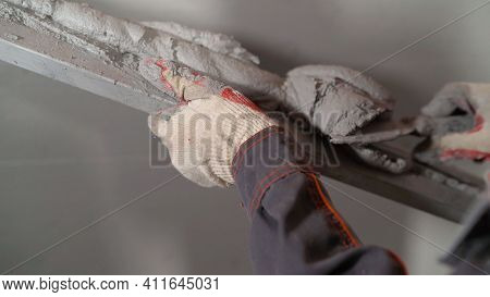 The Worker Applies The Mortar To The Wall With A Wire. Spatula With Mortar. Construction Worker Puts