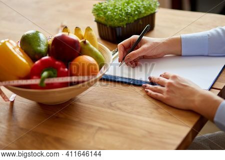 Nutritionist, Dietitian Woman Writing A Diet Plan, With Healthy Vegetables And Fruits