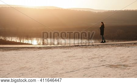 Young Female In Outerwear Walking On Path Near Lake Water Alone In Cold Evening In Outskirts