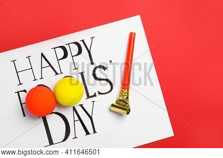 Sheet Of Paper With Phrase Happy Fools' Day, Clown Noses And Party Blower On Red Background, Flat La