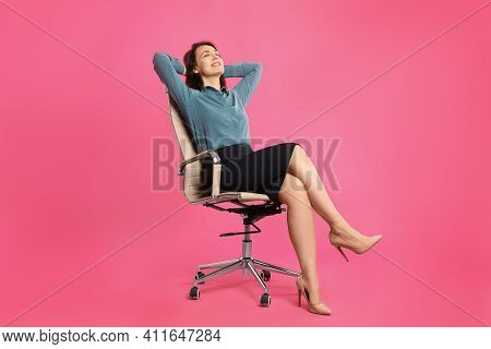 Mature Businesswoman Relaxing In Comfortable Office Chair On Pink Background