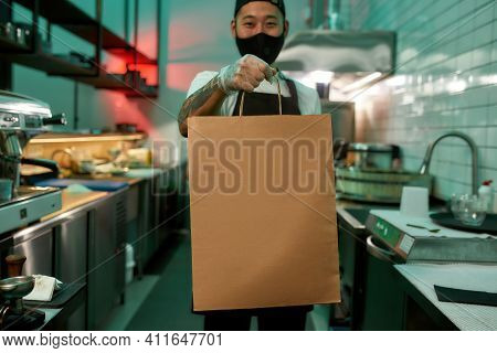 Young Man Standing In A Restaurant With A Large Package Of Food. Food For Delivery During Quarantine
