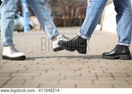 People Greeting Each Other By Bumping Feet Instead Of Handshake Outdoors, Closeup