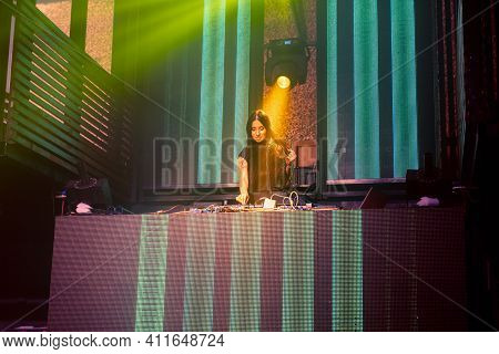 Dj On Stage In Disco Night Club Mixing Techno Music Beat . Nightlife And Dance Party .