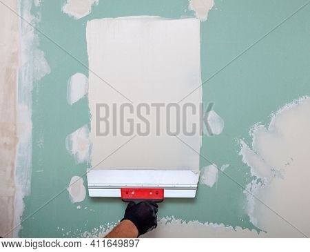 Hand with a spatula. Worker trowels putty on drywall with finishing putty