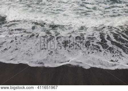 Waterscape Background. Black Sand Beach With White Milky Foam Waves. Nature And Environment Concept.