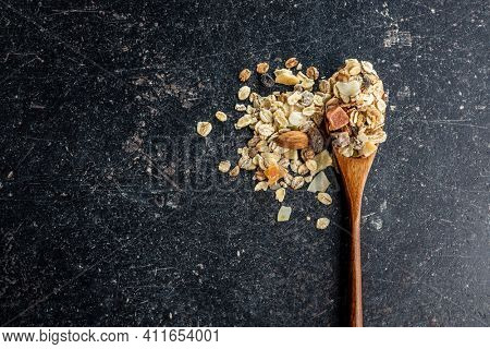 Beakfast cereals in wooden spoon. Healthy muesli with oat flakes, nuts and raisins