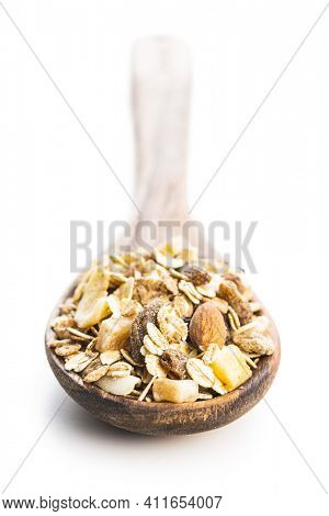 Beakfast cereals in wooden spoon. Healthy muesli with oat flakes, nuts and raisins isolated on white background.
