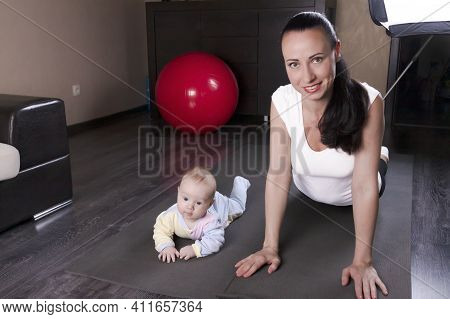 A Beautiful Young Mother With Her Son Goes In For Sports, Yoga, Exercises, Physical Education. The C