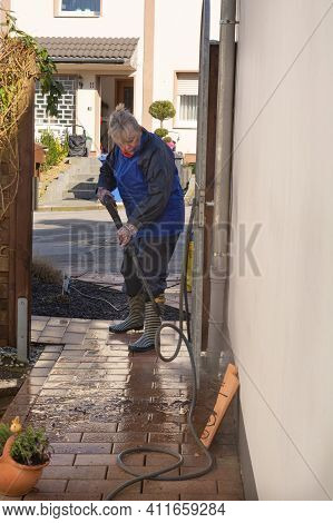 Woman Cleaning Terrace With A Power Washer - High Water Pressure Cleaner On Wooden Terrace Surface