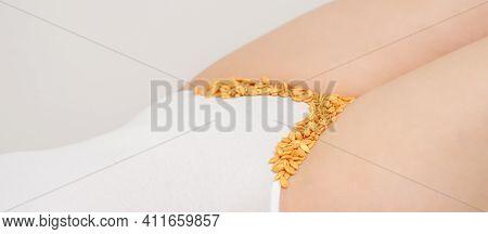 Depilation Of The Bikini Area. Bikini Zone Of A Young Woman With Wax Hard Beans Lying Down On A Whit