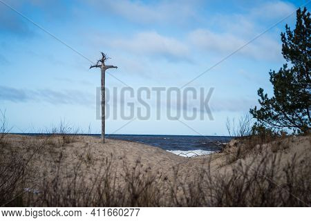 Wooden Cross On The Sea Shore, Placed On A Dune Plateau On A Warm Spring Day With A Blue Sky, Melted