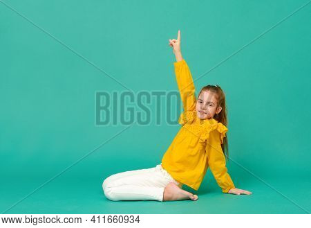 1 Teenage Girl 10 Years Old In A Yellow Blouse Sits On The Floor And Shows Her Hand Up On A Green Ba