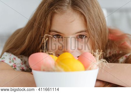 1 White Cute European Girl 10 Years Old With Yellow And Pink Easter Eggs Close Up