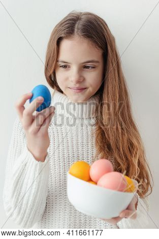 1 White Cute European Girl 10 Years Old With Blue Yellow And Pink Easter Eggs In A White Sweater On