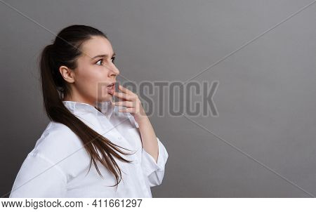 1 White Young Woman 20 Years Old In A White Shirt Is Surprised On A Gray Background