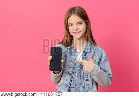 1 Cute White Girl 10 Years Old In A Blue Denim Jacket With A Smartphone In Her Hands On A Pink Backg
