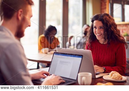 Business Couple With Laptops Having Informal Meeting In Coffee Shop