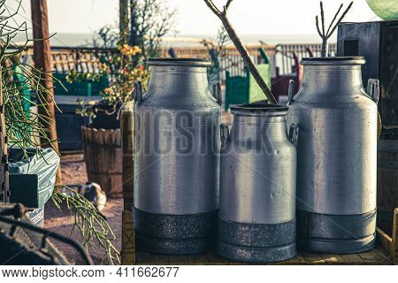 Large Old Metal Milk Cans In The Beautiful Setting Of The Sun.