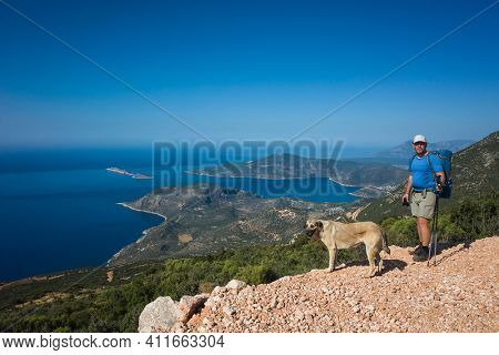 Hiking Lycian way. Man tourist and dog stand on path over Mediterranean sea coast on Lycian Way trail on stretch between Kalkan and Kas, Trekking in Turkey, outdoor activity