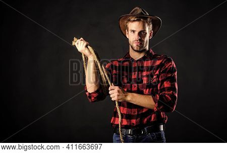 Western Life. Man Unshaven Cowboy Black Background. Man Wearing Hat Hold Rope. Lasso Tool Of America
