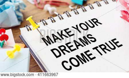 Make Your Dreams Come True - Text On A Notepad With Wrinkled Paper And Paper Needles On Wooden Backg