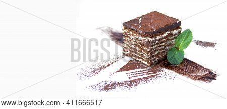 Piece Of Chocolate Cake With Cream With Decorative Elements Of Cocoa And Mint On A White Plate, Choc