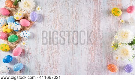 Happy Easter! Colourful Of Easter Eggs With Flower On Pastel Blue Wooden Background. Greetings And P
