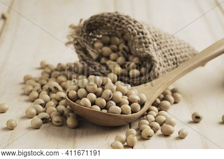 Soybean Seed In Wooden Spoon And Sack On Table With Copy Space. Soybean Is Healthy Diet Food Which H