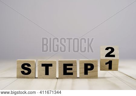 Flipping Wooden Cubes Block For Changing Step 1 To Step 2 On Wooden Table.
