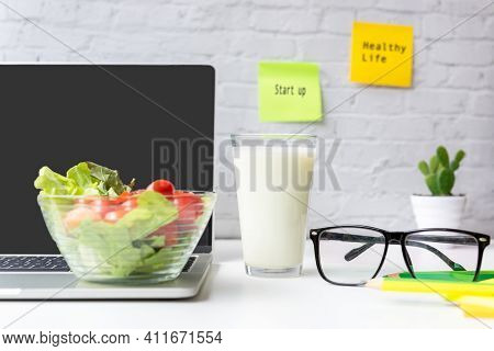 Select Focus. Healthy Snack With Working In The Office.  Green Apple And Fresh Salad With Milk For D