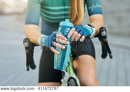 Cropped Shot Of Professional Female Cyclist Holding Water Bottle, Resting, Standing With Her Bike Ou