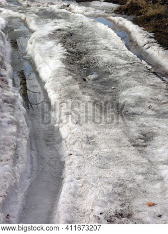 Snowy Road With A Melted Track. Slush. Spring Concept.