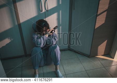 Depressed Suicidal Woman Sitting On The Floor In The Dark, Holding A Gun And Crying, Thinking About