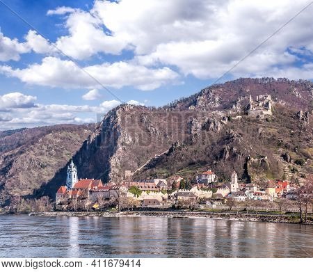 Durnstein Village During Spring Time With Ruin Of Castle On The Rock Over Danube River In Wachau, Au