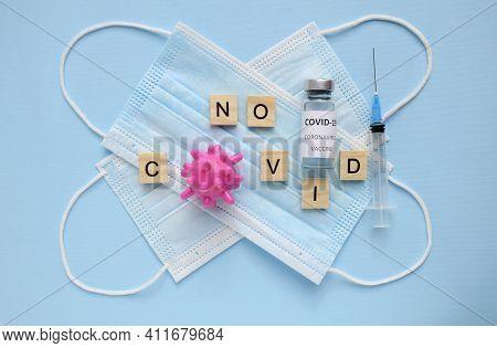 Two Medical Masks, Syringe, Vaccine Bottle On Blue Background. Inscription No Covid. Cured Of Corona