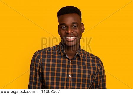 Portrait Of Positive African American Male Student In Checkered Shirt Looking And Smiling At Camera,