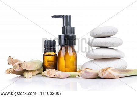 Lemongrass Essential Oil Extract In Bottle With Fresh Lemongrass Plant.