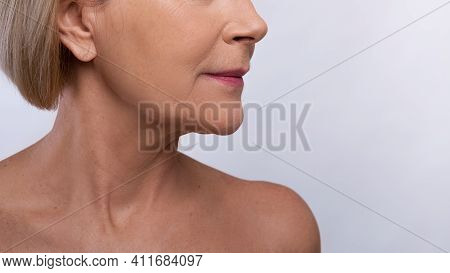 Mature Skin Rejuvenation Concept. Cropped View Of Mature Lady With Naked Shoulders On Grey Studio Ba