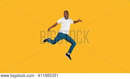 Positive African American Guy Jumping And Shouting Posing In Mid-air Over Yellow Background, Looking