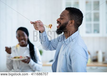 Cheerful Black Man Tasting Spaghetti While Having Lunch With Wife In Kitchen, Romantic African Ameri