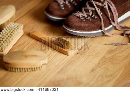 Top View Footwear With Suede Shoe Boots Care Accessories, Brush On Wooden Table.