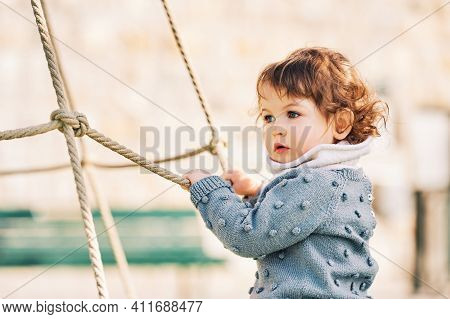 Outdoor Portrait Of Adorable Toddler Girl Having Fun On Playground, 1 - 2 Year Old Kid Playing In Pa