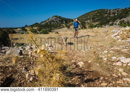 Hiking Lycian way. Man and dog trekking on Lycian Way trail on stretch between Kalkan and Kas, Trekking in Turkey, outdoor activity